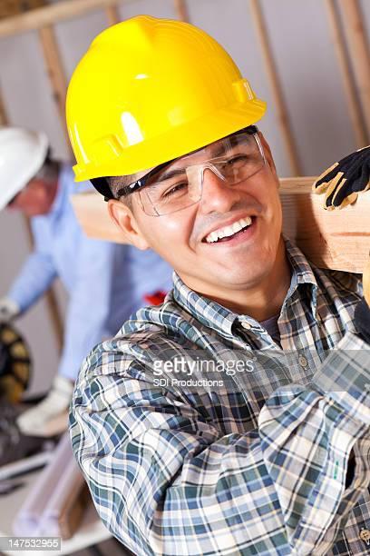 Arbeiter tragen Holz auf Baustelle