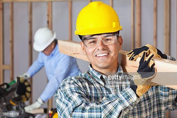 Arbeiter tragen Holz auf Bauten Website