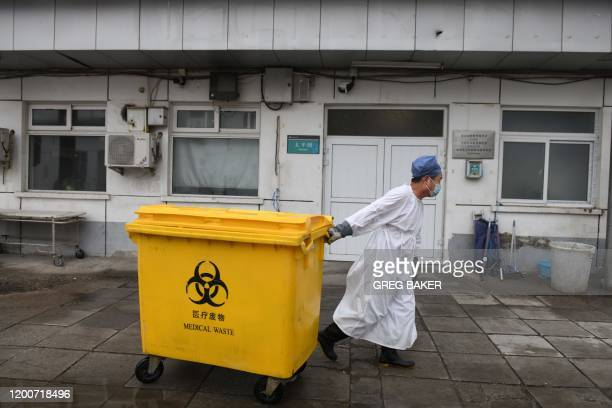 Worker carts a bin loaded with medical waste past the mortuary, to a storage facility at the Youan Hospital in Beijing on February 14, 2020. - Youan...