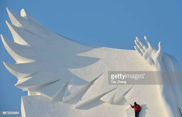 A worker carves the main sculpture 'Snow song Winter Olympics' for the 30th Harbin Sun Island international Snow Sculpture Art Exposition on December...