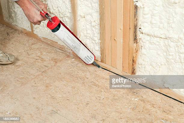 Worker Caulking Wall Plate to Subfloor