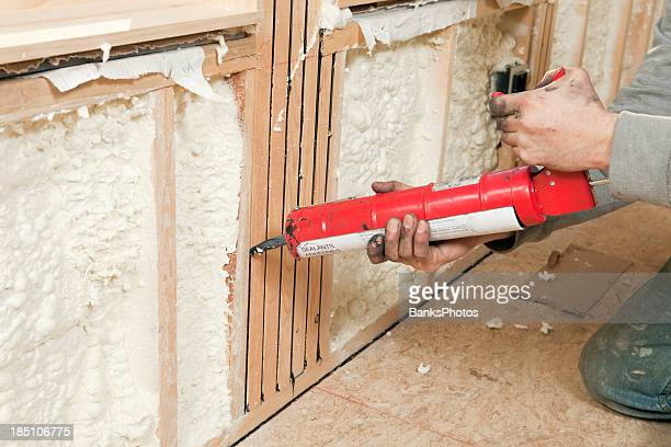 Worker Caulking Wall Studs