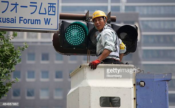 A worker changes lightemitting diode lights on a traffic signal in Tokyo Japan on Friday Aug 21 2015 Japanese stocks plunged with the Topix index...