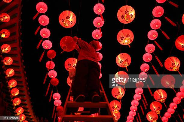 A worker changes the lights bulbs in lanterns ahead of Chinese New Year celebrations at the Thean Hou Temple in Kuala Lumpur on February 9 2013...