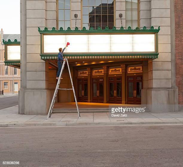 worker changing theater marquee - estreia imagens e fotografias de stock