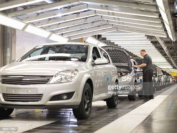 Worker Checking Cars On Production Line