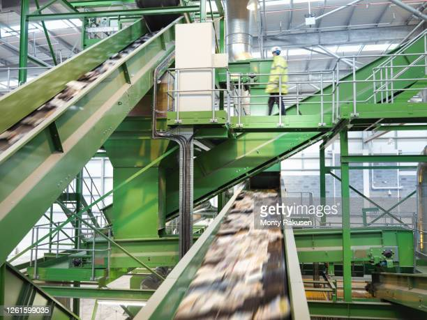 worker checking conveyor belts with waste paper in waste recycling plant. - industry stock pictures, royalty-free photos & images