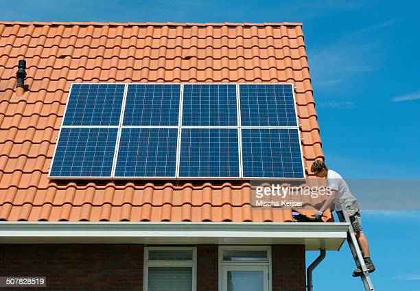Worker checking installation of solar panels on roof of new home, Netherlands