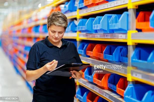 worker checking item from filling tray - industrial storage bins stock pictures, royalty-free photos & images
