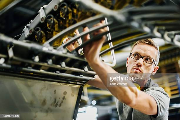 Worker checking machine parts of a conveyor