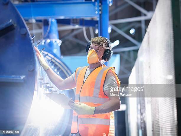 worker checking metal ore grinding mill - mascherina antipolvere foto e immagini stock