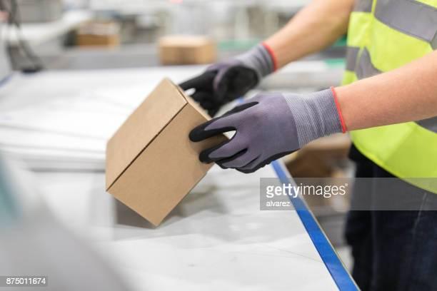 Arbeiter überprüfen Pakets vom Förderband in Lager