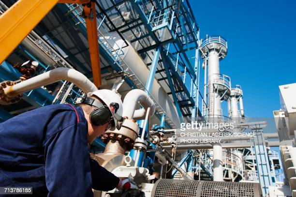Worker checking pipework on an oil and gas refinery
