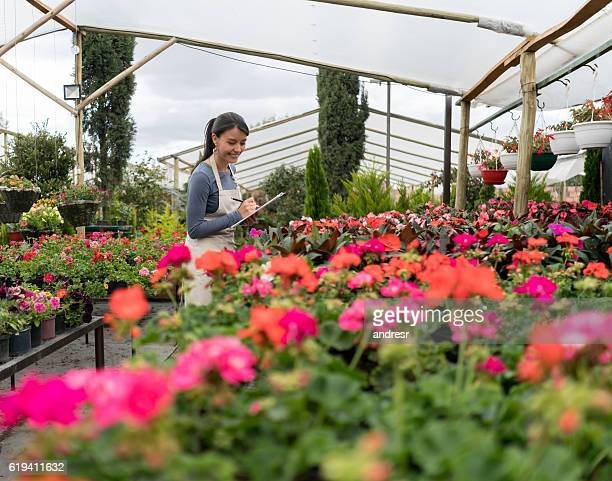 Worker checking plants at a garden center