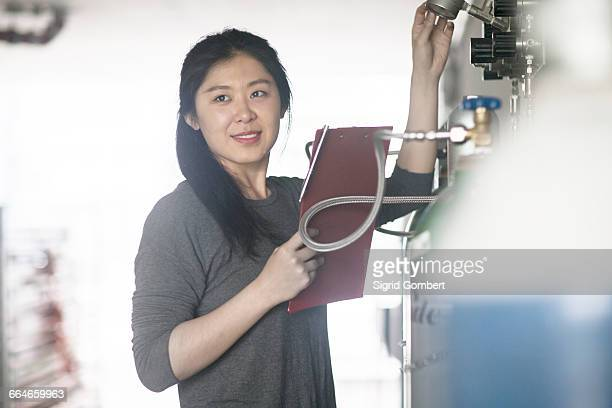 worker checking readings on machine in factory - sigrid gombert stock pictures, royalty-free photos & images