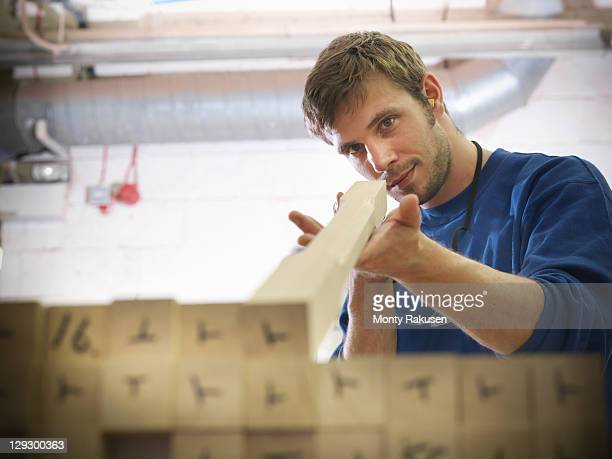 Worker checking staircase bannister railings in joinery