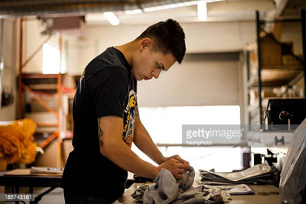 worker checking textiles in screen printing workshop - heshphoto stock pictures, royalty-free photos & images
