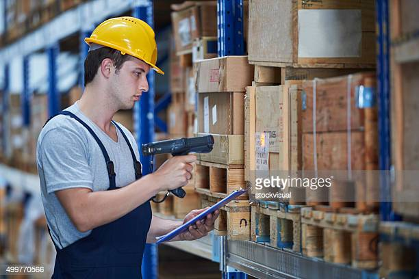 Worker checking the storages with barcode terminal in warehouse