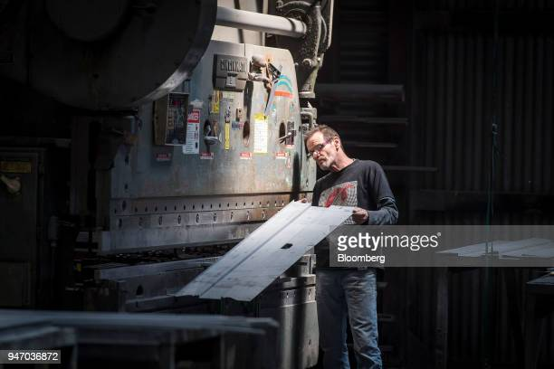 A worker checks a bend on a piece of metal made using the press brake at the Metal Manufacturing Co facility in Sacramento California US on Thursday...