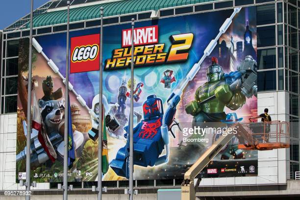 A worker checks a billboard for Marvel Entertainment LLC and Lego A/S Super Heroes 2 video game displayed outside the Los Angeles Convention Center...