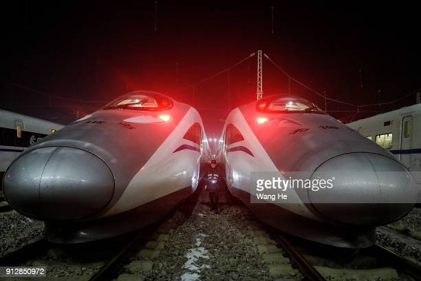 A worker checks a CRH bullet train at the maintenance base on the first day of the 40day Spring Festival Travel Peak on February 1 2018 in Wuhan China