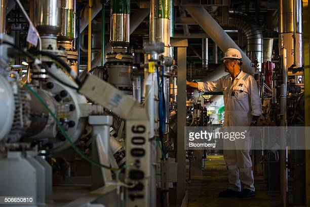 A worker checks a dial on the Tullow Oil Plc Prof John Evans Atta Mills Floating Production Storage and Offloading vessel docked at the Sembcorp...