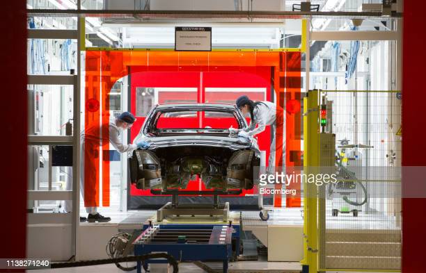 A worker checks a MercedesBenz EClass automobile body after painting on the production line at the Daimler AG luxury automobile plant in Moscow...