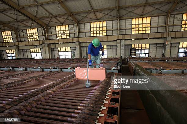 A worker checks a sheet of electrolytic copper in a tankhouse at the Onahama Smelting Refining Co plant in Iwaki City Fukushima Prefecture Japan on...