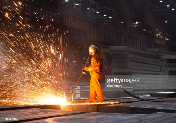 A worker checks and cleans steel slabs in a storage area at the converter shop at the Novolipetsk Steel PJSC plant operated by NLMK Group in Lipetsk...