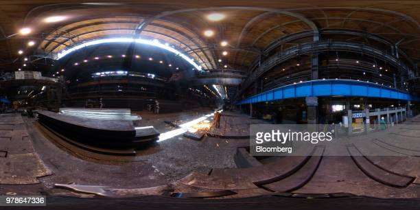 A worker checks and cleans steel slabs in the converter shop at the Novolipetsk Steel PJSC plant operated by NLMK Group in Lipetsk Russia on Monday...