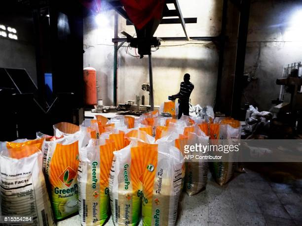 A worker checks bags of processed rice at a local rice mill in northern Nigerian city of Kano on June 30 2017 / AFP PHOTO / AMINU ABUBAKAR