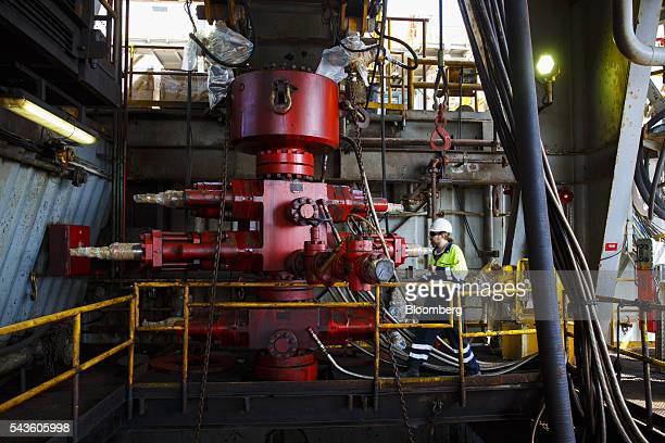 A worker checks equipment on the towel deck of the Casablanca oil platform operated by Repsol SA in the Mediterranean Sea off the coast of Tarragona...
