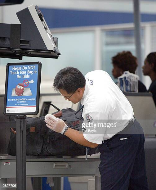TSA worker checks for traces of explosives on a traveler's suitcase at O'Hare International Airport December 22 2003 in Chicago US authorities have...