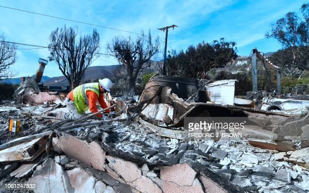 A worker checks gas lines amid the rubble of a home burnt down in the Woolsey Fire on Filaree Heights Road in Malibu California on November 13 2018...