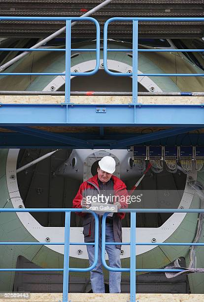 A worker checks his clipboard while standing in front of the nose of an Airbus A380 passenger plane at the IMA and IABG testing facility April 5 2005...