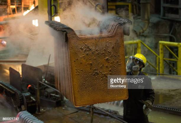 A worker checks newlycast copper anode sheets at the MMC Norilsk Nickel PJSC copper refinery in Norilsk Russia on Thursday Oct 19 2017 Norilsk Nickel...