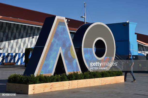 A worker checks on a logo for the Australian Open tennis tournament ahead of its start in Melbourne on January 14 2018 / AFP PHOTO / PETER PARKS /...