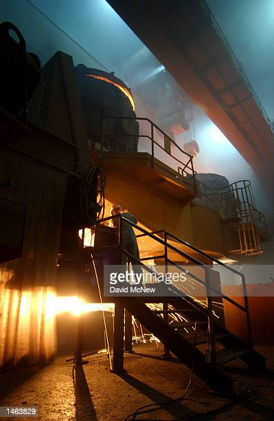 A worker checks on the flow of molten steel at the TAMCO steel mini mill on October 4 2002 in Rancho Cucamonga California TAMCO California's only...