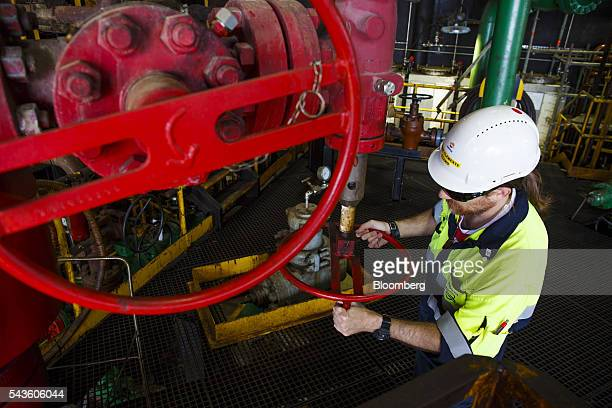 A worker checks pipework valves on the towel deck of the Casablanca oil platform operated by Repsol SA in the Mediterranean Sea off the coast of...