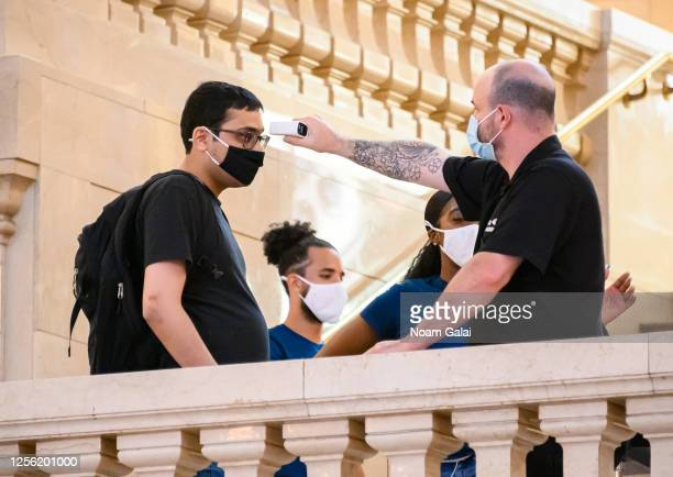 A worker checks the body temperature of a customer outside the Apple Store in Grand Central Terminal as the city moves into Phase 3 of reopening...