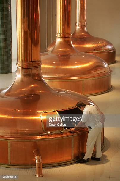 A worker checks the brew consisting of heated barley mash known as wort mixed with hops and cooking in giant copper vats that will become...