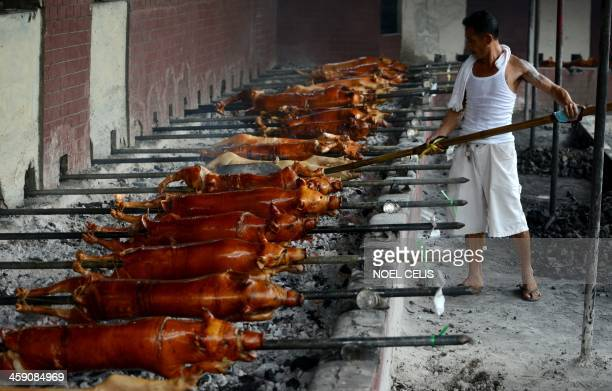 A worker checks the coal as he roasts pigs in Manila on December 23 2013 for the busy holiday season 'Lechon' or roasted pig has always been a...