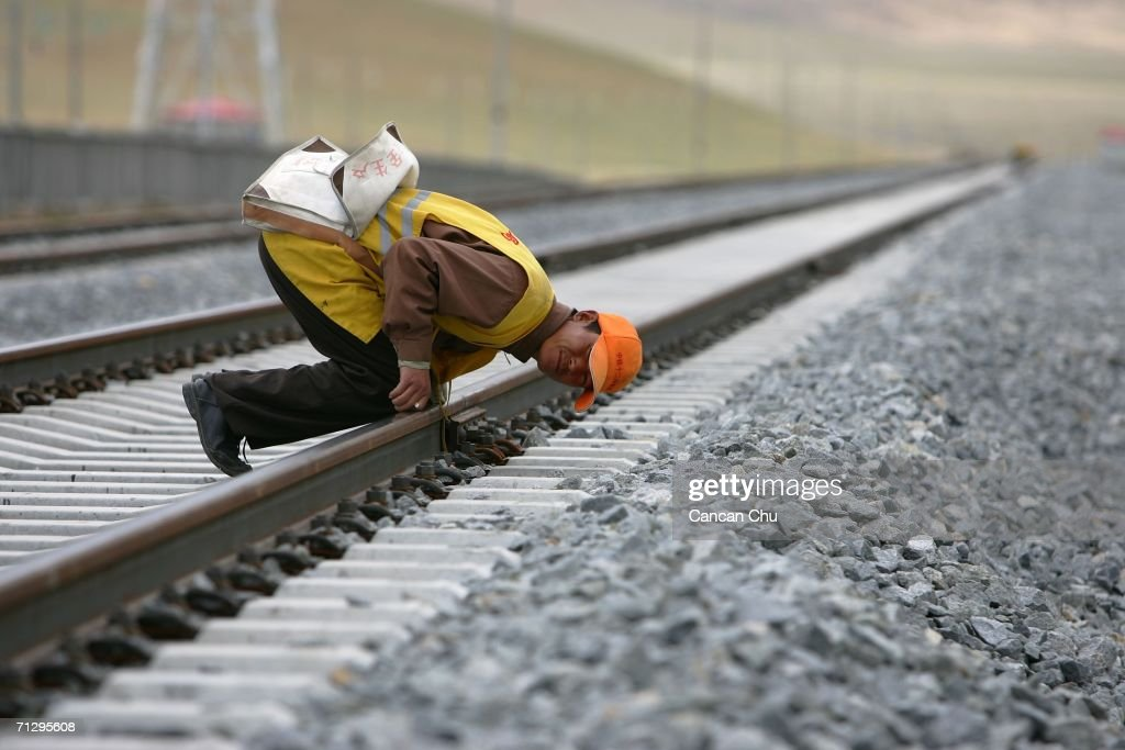 A worker checks the Dangxiong-Lhasa section of the Qinghai-Tibet Railway on June 25, 2006 in Dangxiong County of Lhasa, Tibetan Autonomous Region, China. The Qinghai-Tibet railway will begin trial operations on July 1 and schedule has been set for the first five trains to Tibet via the new railway, an official with the Qinghai-Tibet Railway Company said. The 1,956-kilometer-long (about 1,215 miles) Qinghai-Tibet railway, linking Xining, capital of Qinghai Province, with Lhasa, capital of Tibet Autonomous Region, is the world's highest and longest plateau railroad and also the first railway connecting Tibet with other parts of China. Some 960 kilometers (576 miles) of its track are located 4,000 meters (13,120 feet) above sea level and the highest point is 5,072 meters (16,636 feet), according to state media.