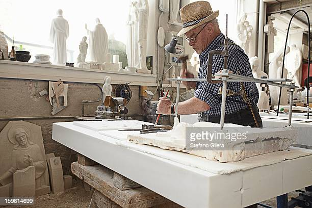 Worker chiseling slab of stone