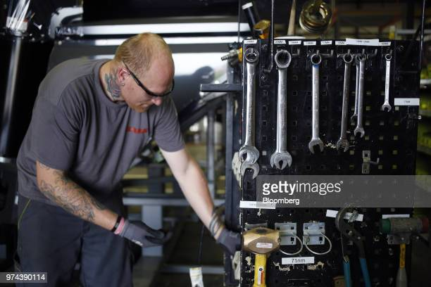 A worker chooses a tool while assembling a combine harvester at the CLAAS of America Inc production facility in Omaha Nebraska US on Wednesday June 6...
