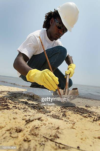 Worker clean up oily globs that washed ashore from the Deepwater Horizon oil spill in the Gulf of Mexico July 9, 2010 in Waveland, Mississippi....