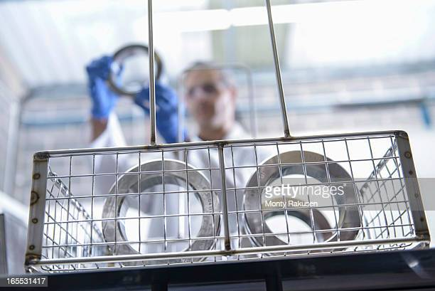 Worker cleaning engineering products using ultrasonics, focus on foreground