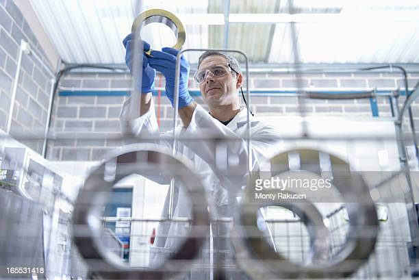 Worker cleaning engineering products using ultrasonics, focus on background