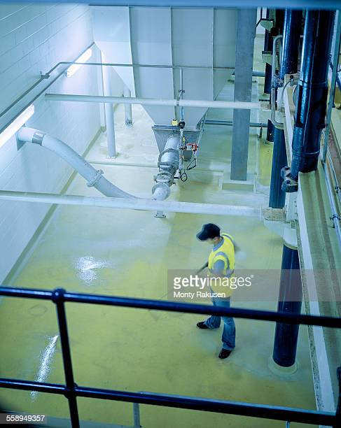 Worker cleaning floor and equipment in brewery, high angle view