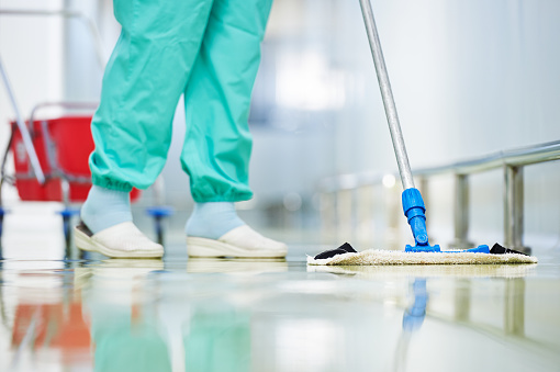 worker cleaning floor with mop 501190742